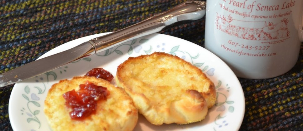A toasted English muffin with red jam sits on a white plate beside a Pearl of Seneca Lake mug