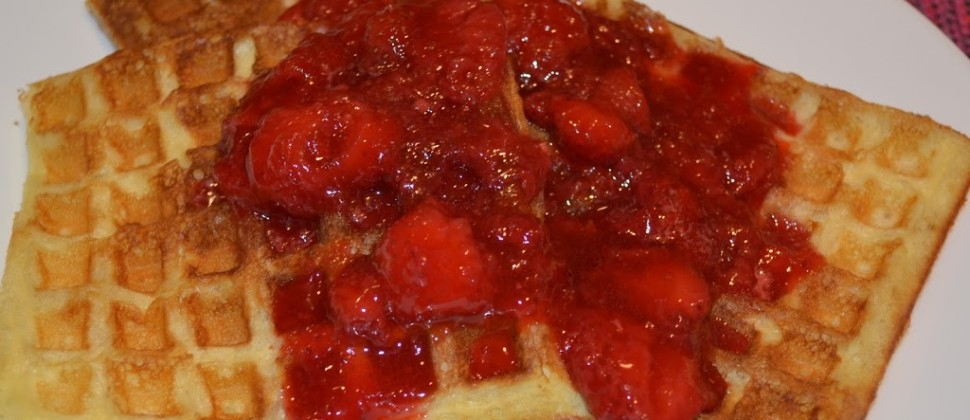 Golden waffles topped with bright red strawberries and strawberry syrup rest on a white plate