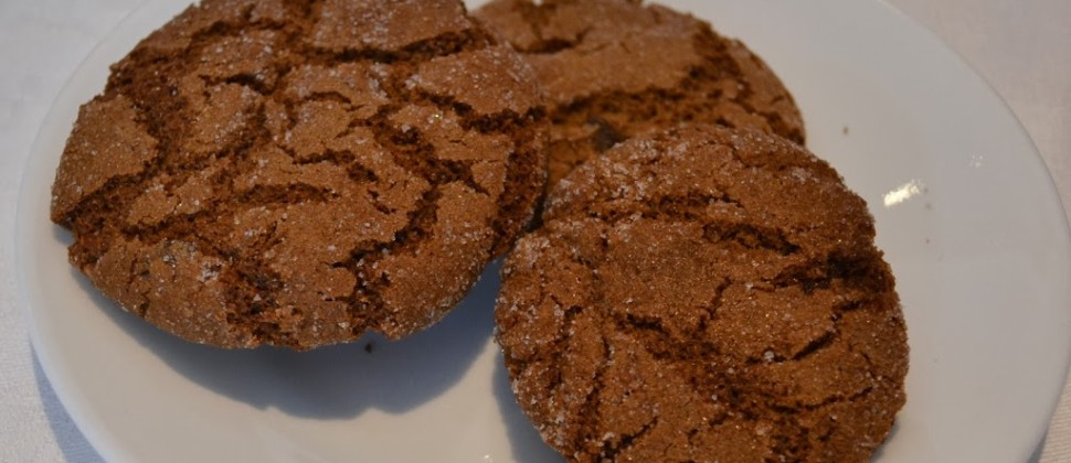 Three brown sugar-topped ginger cookies rest on a white plate