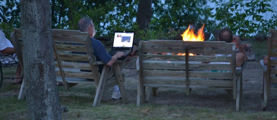 Two men enjoy the bright orange campfire while sitting in brown outdoor benches; one uses a laptop