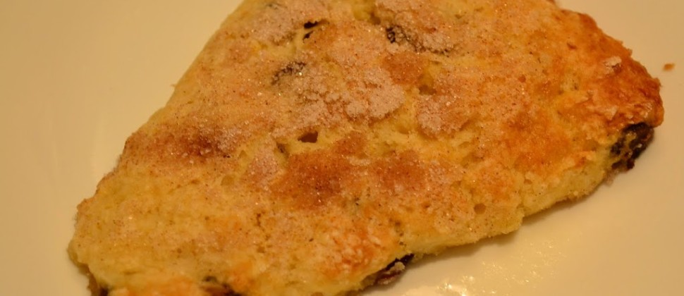 A golden cherry and walnut scone adorned with cinnamon and sugar sits on a white plate