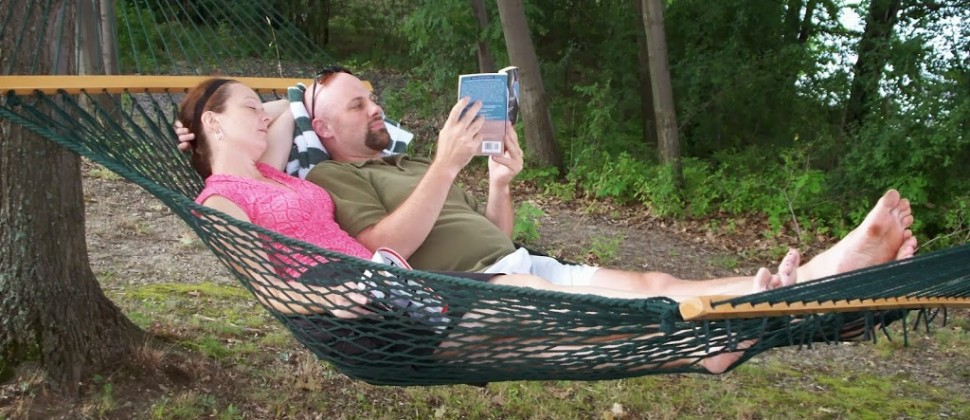 A man and a woman relax together in a green hammock while reading a book