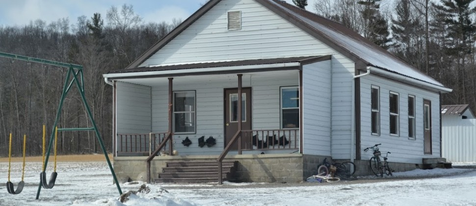 A white Mennonite school in a snowy landscape with rubber boots hanging in the front porch area