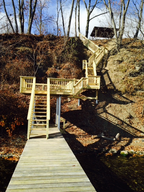 Wooden stairs going down to an 80-foot dock under blue skies