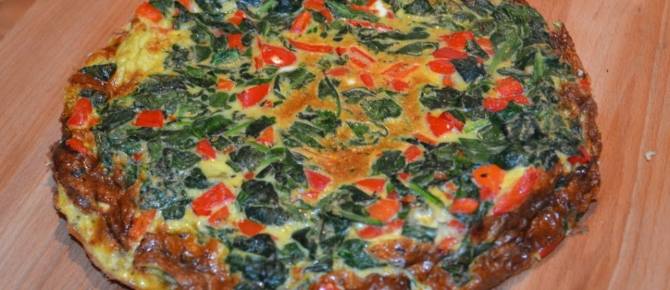 Green spinach, red tomatoes and melted cheese are baked into a golden frittata