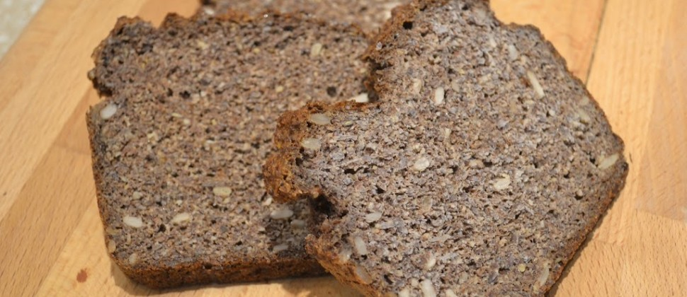 Slices of hearty, grainy brown bread sit atop a wooden cutting board