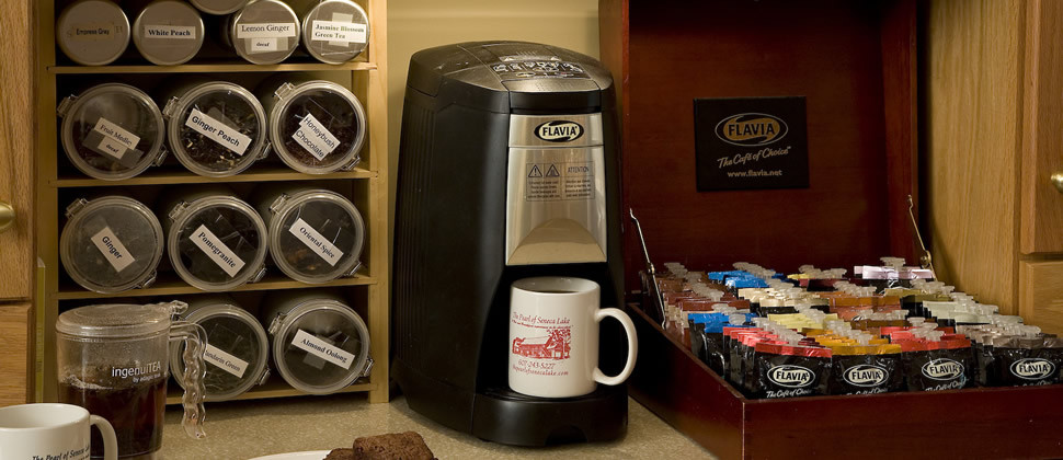 A tea station features a single-cup tea brewer and a very large variety of teas to choose from