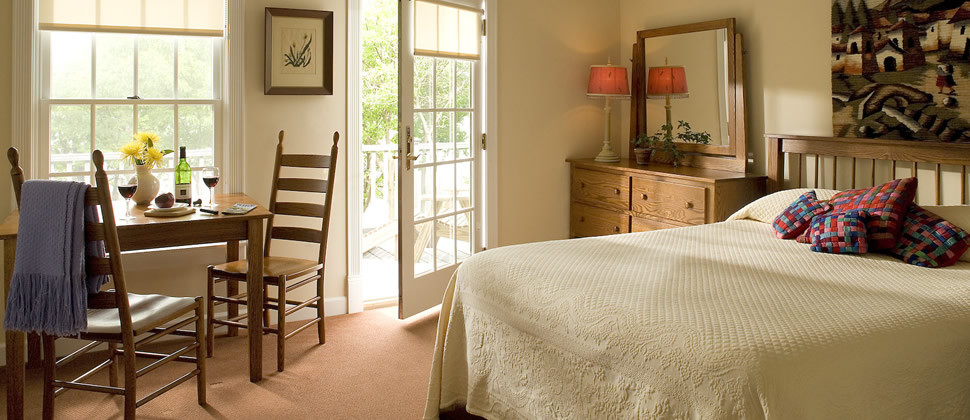 Guestroom with brown carpet, cream walls, wooden sitting table, wooden dresser and king bed with tapestry throw pillows