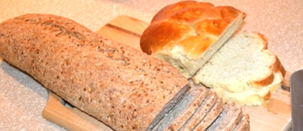 Partially-slice homemade white bread and multi-grain bread sit on a wooden cutting board