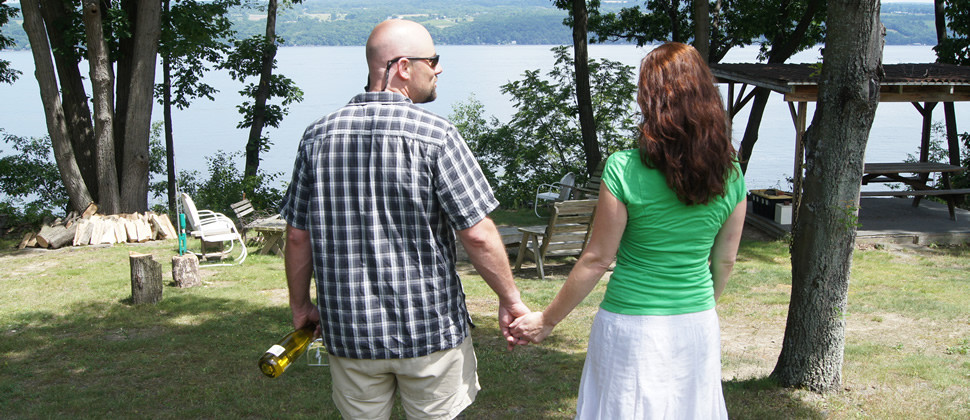 A man an woman hold hands while facing a blue lake on in a wooded backyard setting
