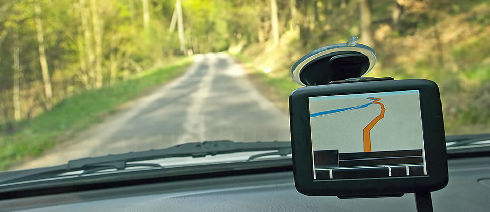 A GPS mounted on a car's windshield points the way down a rural wooded road