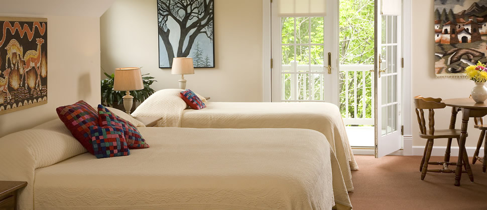 A large bedrooms with brown carpet, two beds with cream bedspreads and an open door to a deck