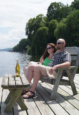 A couple rest on a lake dock's wooden bench chair ; a bottle of white wine on the table nearby