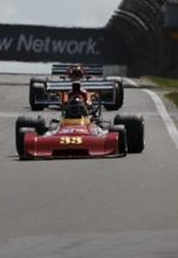 Two Formula Cars, one red and one blue, race on a paved track