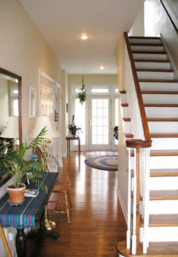 A home's entryway with wood flooring looks through to rear white french doors, a stairway on right leading up