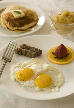 A hearty breakfast of two eggs, two sausage links, pancakes and fruit on white plates